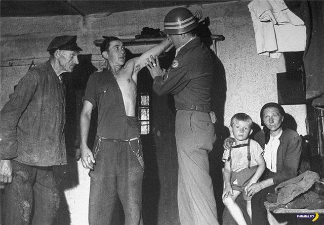 Американский солдат рассматривает немецкого пацана